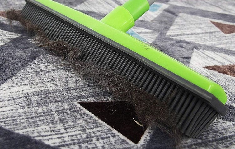 cleaning carpet with rubber broom