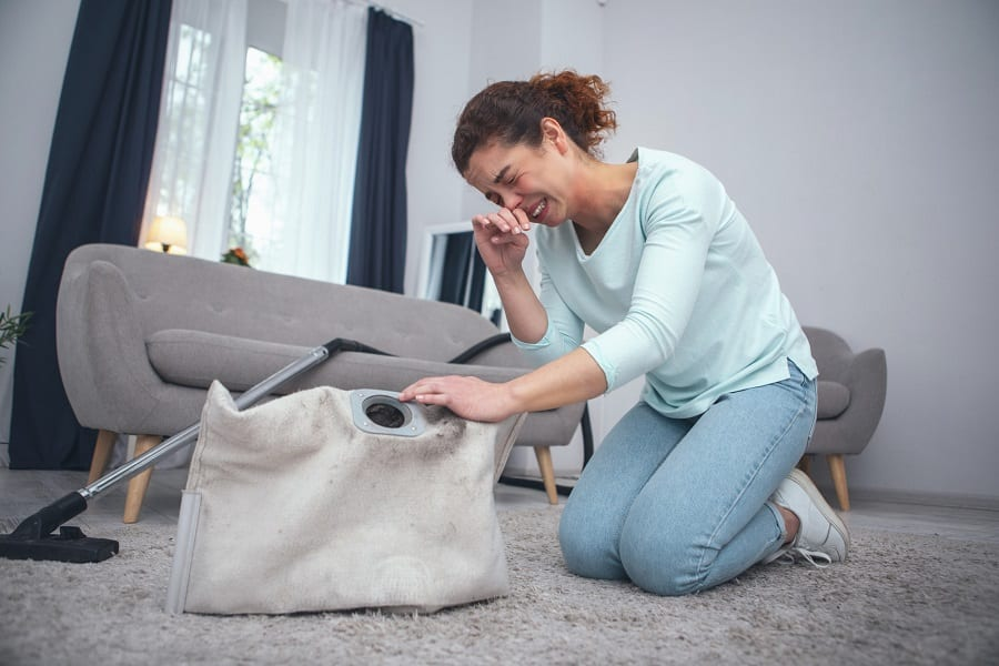 Young lady cleaning smelly carpet suffering from dust allergy