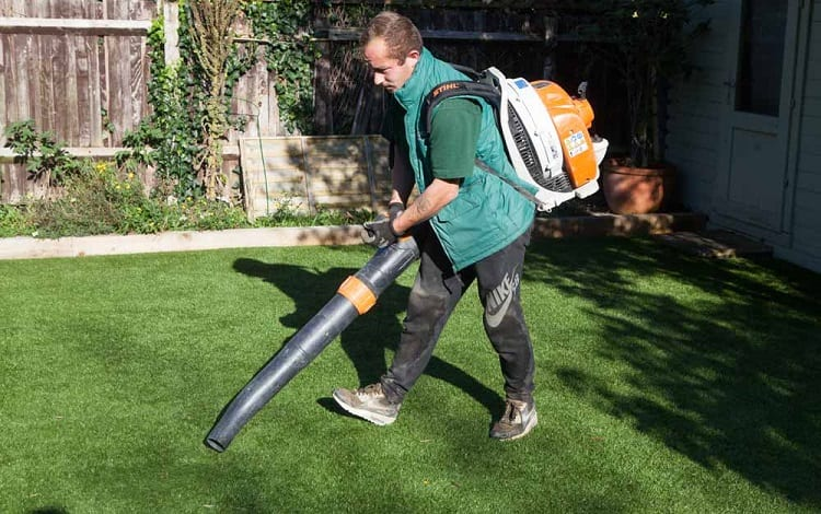 man cleaning leaves from artificial grass