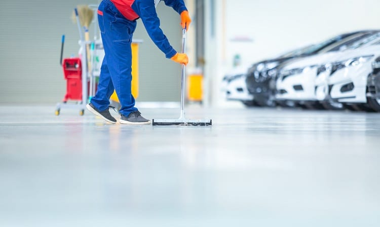 mechanic cleans epoxy floor